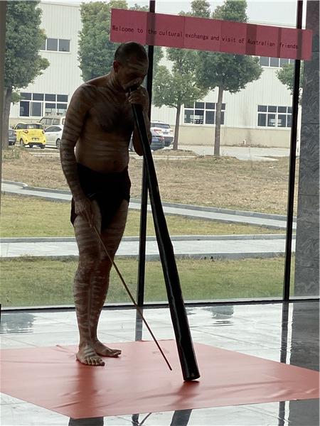 Australian clients perform Aboriginal instruments to employees